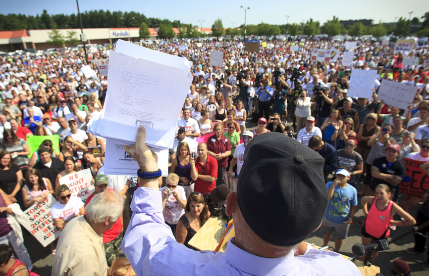 Steve Paulenka, who was fired from Market Basket during the protests, held up a stack of petitions he said were signed by customers in support of bringing back the former CEO Arthur T. Demoulas. (Dina Rudick/The Boston Globe)